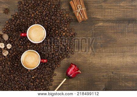 Two cups of coffee with a foam top view. Coffee beans badon cinnamon and caramel on a wooden surface with place for text. Love of a coffee drink with copy space. Morning invigorating coffee for two.