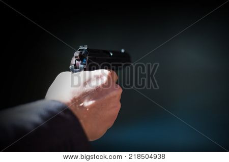 Shot of a pistol in the hands of a man . Shallow depth of field. Close-up.