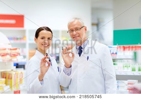 medicine, healthcare and technology concept - happy smiling apothecaries at pharmacy showing ok hand sign