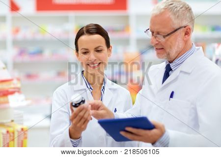 medicine, healthcare and technology concept - apothecaries with tablet pc computer and medication at pharmacy
