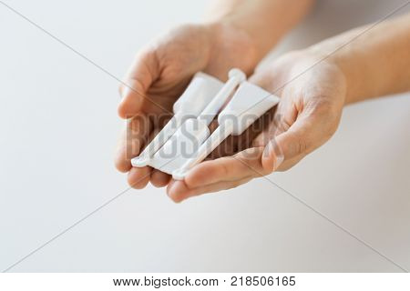 medicine, healthcare and pharmaceutics concept - hands holding tubes of micro enema