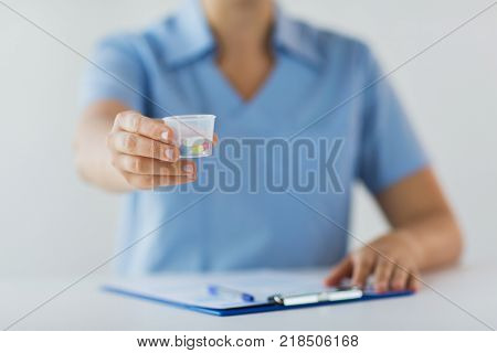 medicine, healthcare and people concept - nurse or doctor with pills in medical cup and clipboard