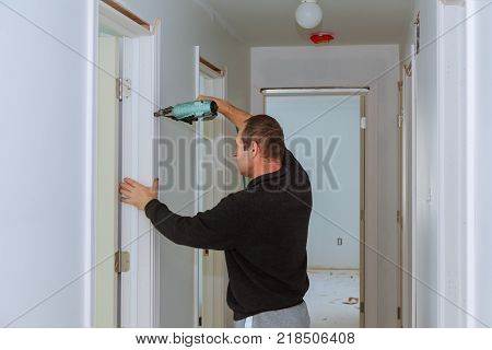 Carpenter brad using nail gun to moldings on doors, framing trim, with the warning label that all power tools have on them shown illustrating safety concept