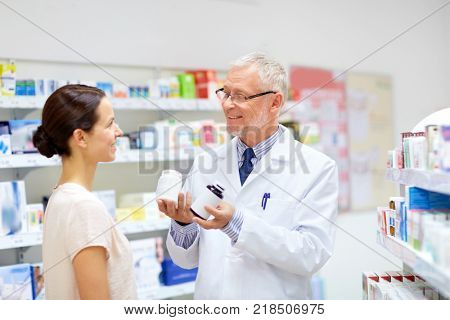medicine, healthcare and people concept - senior apothecary with drugs and female customer at pharmacy