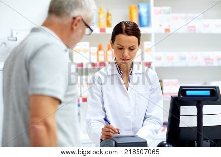 medicine, pharmaceutics, healthcare and people concept - apothecary writing prescription for senior male customer at drugstore