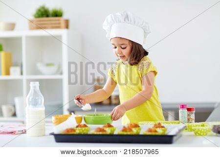 family, cooking, baking and people concept - little girl in chefs toque making batter for muffins or cupcakes at home kitchen