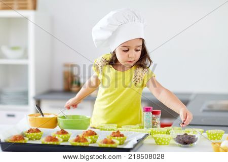 family, cooking and people concept - little girl in chefs toque baking muffins or cupcakes with sprinkles at home