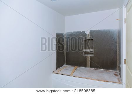 New under construction bathroom interior with drywall and patching new bath installation