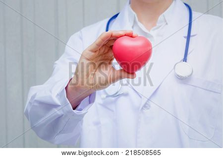 pharmacist or doctor with stethoscope around his neck and hand holding red heart in hospital heart attack pharmacy laboratory research science chemical health care and medical technology concept