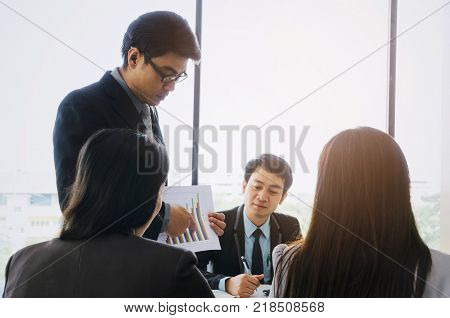 asian project manager showing and presenting growth chart diagram of financial report or results of the year in meeting room at office investment company success and teamwork concept vintage tone