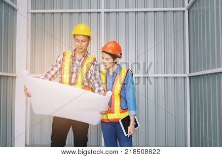 couple of technician man and woman with safety helmet in reflective clothing looking blueprint for new project in building at construction site engineer safety industry and construction concept