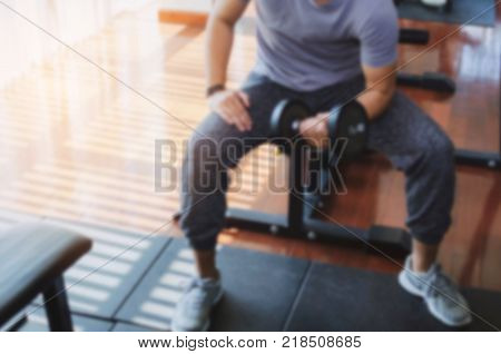 blurred image of muscular asian young handsome man doing the exercises with dumbbell at biceps in fitness gym bodybuilder healthy lifestyle exercise fitness workout and sport training concept