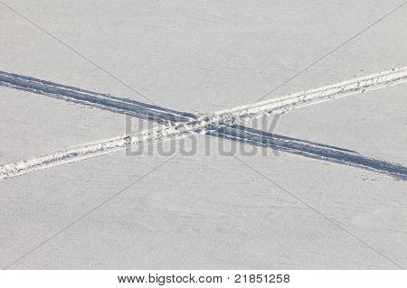 Crossing snowmobil tracks in powder surface