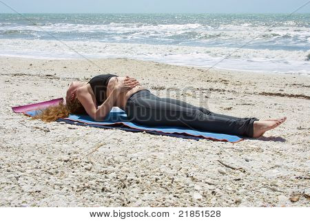 Young Woman Doing Yoga Exercise On Beach In Fish Pose