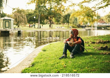 boy sitting on the shore of a pond. child resting near a city pond with ducks. copy space for your text