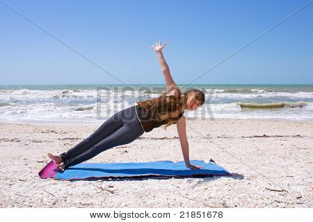Young Woman Doing Yoga Exercise On Beach In Vasisthasana Or Side Plank Pose