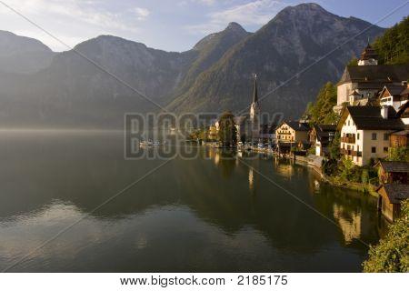 Boat Sailing Into The Morning Fog In Hallstatt, Austria