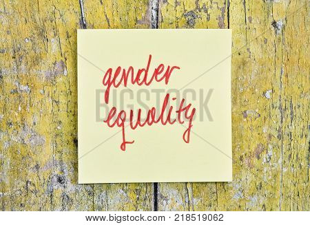 Handwritten text Gender Equality on a sticker pinned on wooden background