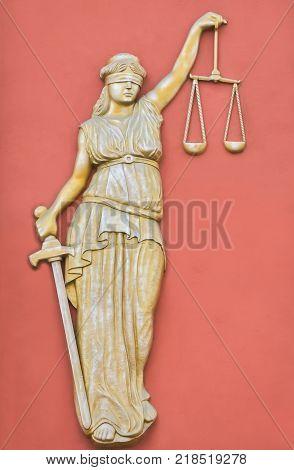 Monument of blind Justitia on orange background