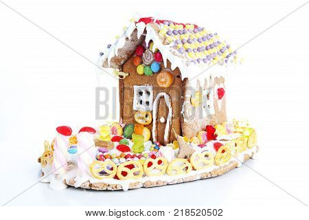 Gingerbread candy sugar house. Fairy tail candyhouse covered with snow and colorful candies Homemade gingerbread house with colorful candy decoration. Christmas ornaments. Cute little christmas house.