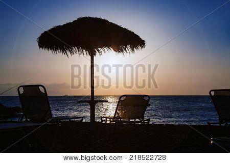 Beach umbrella and sun beds on the sea beach at sunset