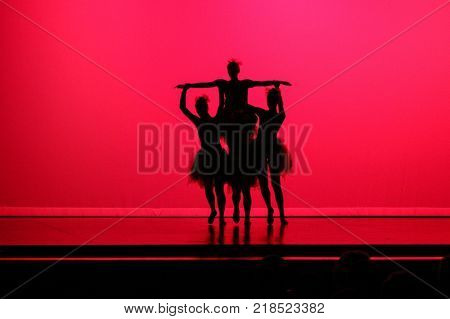 Silhouette of ballet dancers holding a ballerina aloft in front of a red background