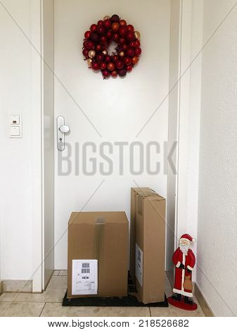 Online Christmas Shopping - parcels in front of an entrance door with Christmas decorations