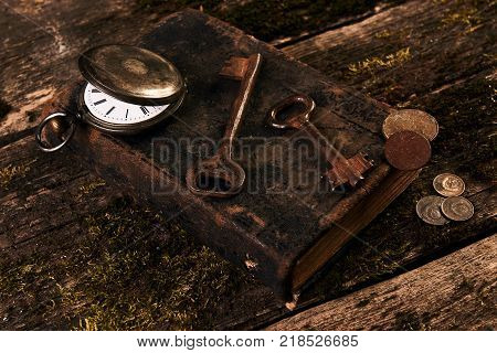 Antique pocket watch, old book with ancient copper coins and brass keys on grunge wooden background. Vintage grunge still life concept. Antiques in an antique shop
