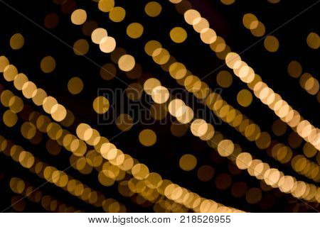 Beautiful Overlay bokeh light texture for design. Golden spot light in row on black background. Decorative Holiday pattern for backdrop. Can use for decoration Festive cards banners flyers.