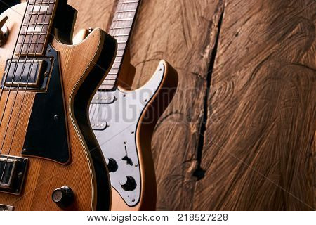 Classic electric guitar and wooden electric bass guitar on wooden background with copy space, string musical instrument, close-up