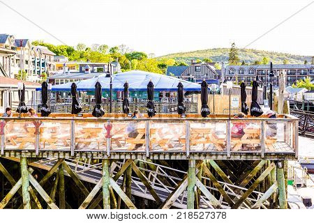 Bar Harbor, USA - June 8, 2017: Wooden deck dock, marina and waterfront restaurant with people eating sitting on chairs by tables in downtown village in summer