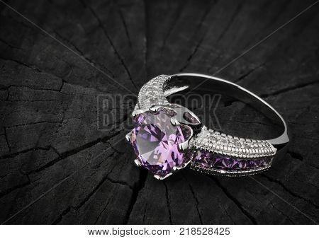 Jewelery ring on black wood background copy-space