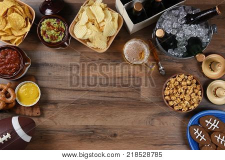 Snacks and drinks laid out for a football watching party. Top view with copy space.