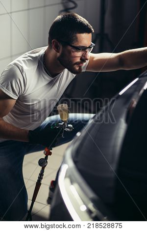 man wear protective mask and eyewear at work.Car Care Business. Car coating business with ceramic coating