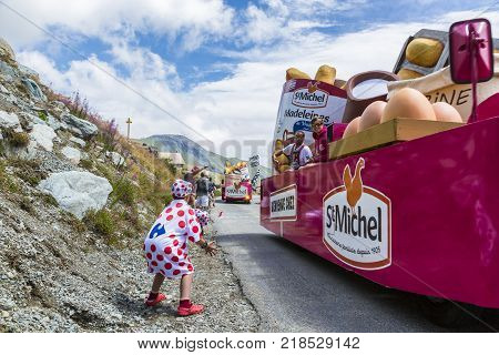 Col de la Croix de Fer France - 25 July 2015: Kid in Polka-Dot Jersey enjoying the passing of the Publicity Caravan on the road to the Col de la Croix de Fer in Alps during the stage 20 of Le Tour de France 2015.