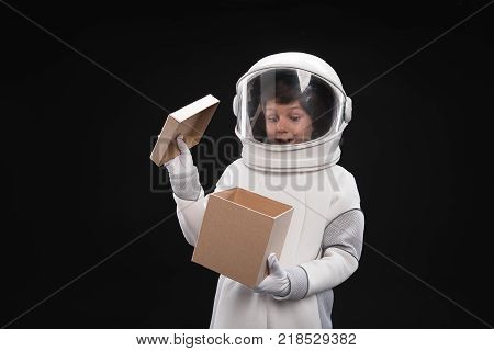 Best surprise. Portrait of little cosmonaut wearing helmet and protective costume is standing and opening cardboard box while feeling wonder and curiosity. Isolated background