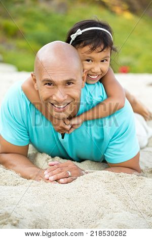 Asian father and daughter laughing and playing on the beach.