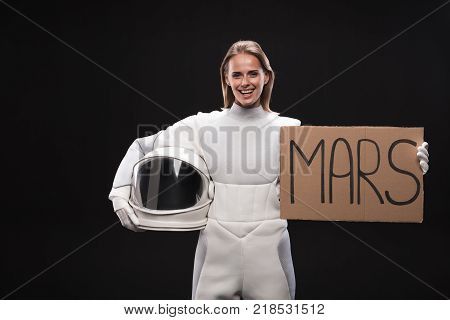 Migration to red planet. Portrait of delighted spacewoman wearing full armor is looking at camera with joy while holding white helmet and mars sign. Isolated background. Resettlement concept