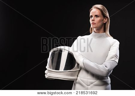 Young lady astronaut wearing protective costume is standing and looking aside wistfully while holding helmet. Isolated background with copy space in the left side. Cosmos concept