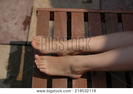 Legs of a young woman on a wooden chaise lounge.
