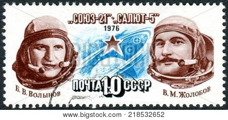 USSR - CIRCA 1976: A stamp printed in USSR dedicated to exploits of Soyuz-21 and Salyut-5 space station shows cosmonauts V. V. Volynov V. M. Zholobov Star Circling Globe circa 1976