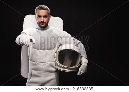 You. Portrait of confident spaceman is standing and pointing on you while looking at camera seriously. He is holding helmet while posing in astronaut protective suit. Isolated with copy space