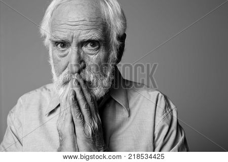 Portrait of frightful pensioner looking at camera while holding hands on mouth. Isolated on grey background. Copy space