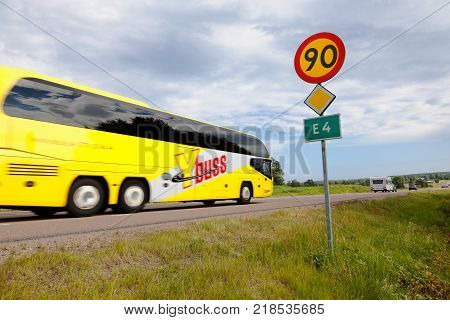 Gnarp Sweden - July 14 2015: Yellow bus in service for Y-buss on road E4 south bound passing a speed limit sign 90 kmh.