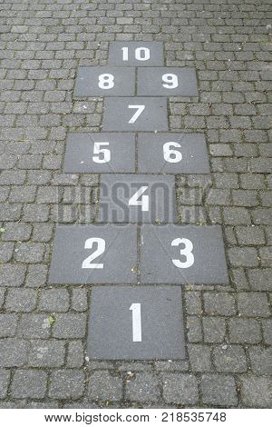 Hopscotch court with numbers from 1 to 10 drawn with white paint on the sidewalk