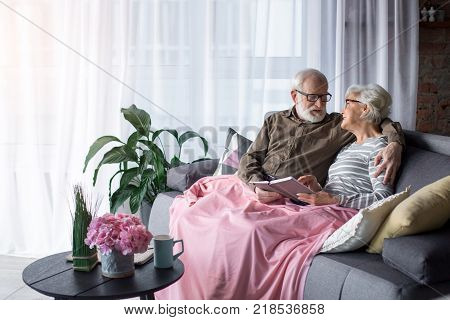 Loving mature couple reviewing old memoirs while relaxing on sofa. Husband is cuddling wife while they are looking at each other and smiling