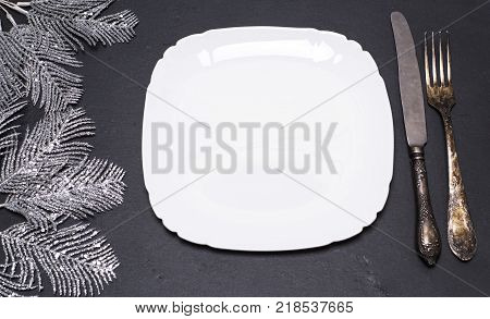 empty white square plate and vintage metal fork and knife on a black background top view