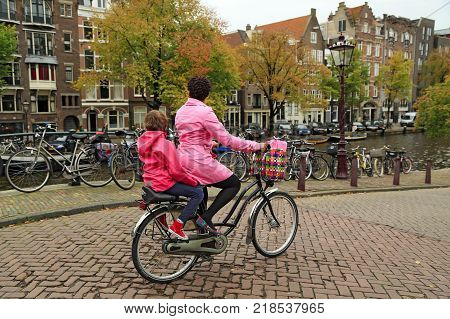 AMSTERDAM/ NETHERLANDS - OCTOBER 25, 2014. A brightly dressed woman on a bicycle, carrying her child on the rear child seat. Embankment of the Prinsengracht canal,   Amsterdam, the Netherlands.