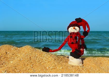 Christmas, Travel, Holidays Concept.Snowman In Red Clothes Standing On The Beach.Happy Snowman at Ocean Beach. Happy New Year and Merry Christmas Traveling Destinations, Tropical Vacations Concept.