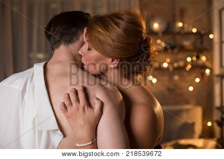 Affectionate loving couple is embracing with desire. Woman is kissing male neck with temptation while nailing into man nude back. Prelude concept